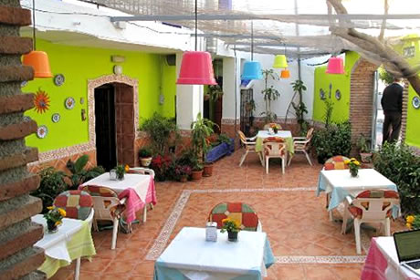 green pation with tables in hostel la herradura