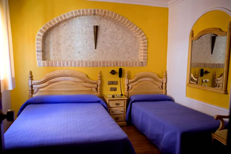 double bed with yellow background wall in campana hostel