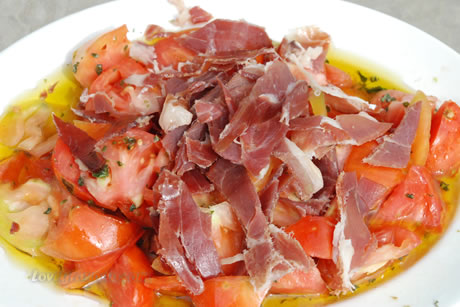 a plate of food parmaham with tomatoes