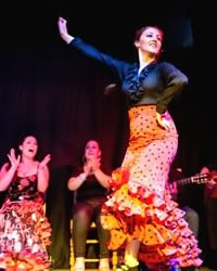 a dancer dances flamenco in granada in red flamenco dress