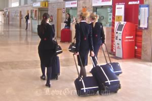 stewardess waling with suitcases in granada airport